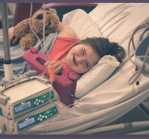 Girl in hospital bed with Ipad and teddy