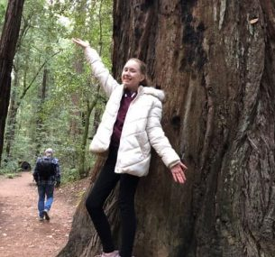 Girl in white jacket in front of tree