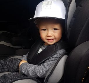 Boy in car seat with cap on