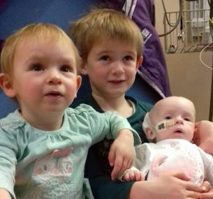 Lucie in hospital with siblings