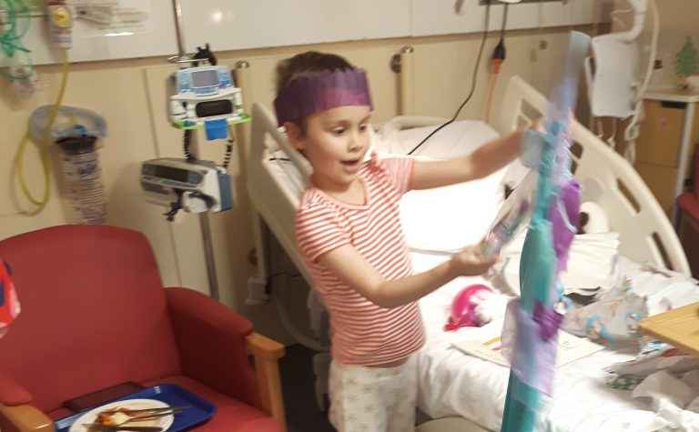 Children opening Christmas presents in hospital