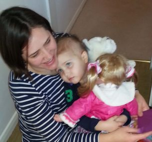 girl cuddling mum with doll