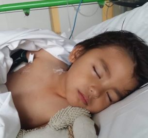 Boy in hospital bed with toy