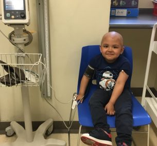 Boy with no hair in hospital chair getting a check-up