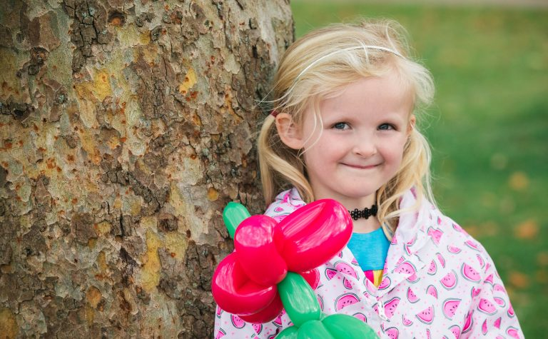 Daisy holding balloons, leaning against a tree