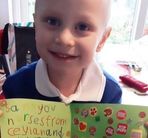 Ceylian with the thank you card he made for the nurses who cared for him during his treatment for Ewing sarcoma.