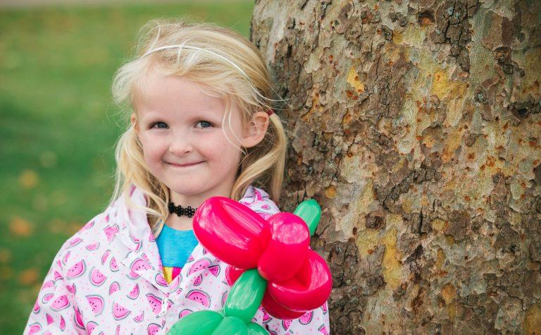Daisy 3 girl next to tree bark and red balloon