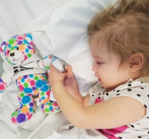 Girl in hospital bed with multi-coloured spotted toy
