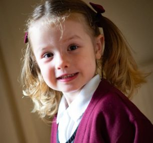 Girl with hair in bows and in maroon school uniform