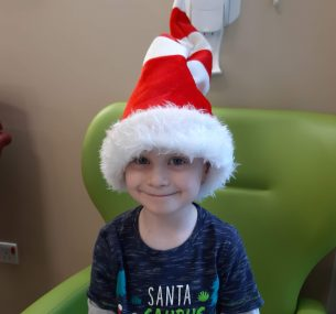 Boy in hospital with christmas hat on