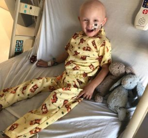 Boy in yellow pyjamas and bunnies in hospital bed
