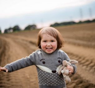 Girl with bunny jumper and toy in field