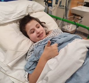 Girl in hospital bed with thumbs up
