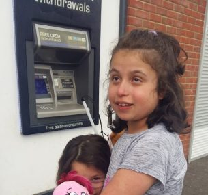 Blind girl in grey top standing outside cash point