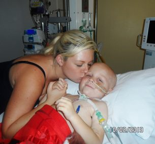 mum kissing son Blake by hospital bed