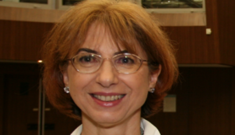 Female researcher with glasses smiling at camera Eva Steliarova Foucher