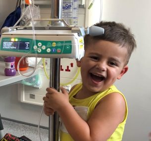 Smiling boy in yellow top holding machine in hospital
