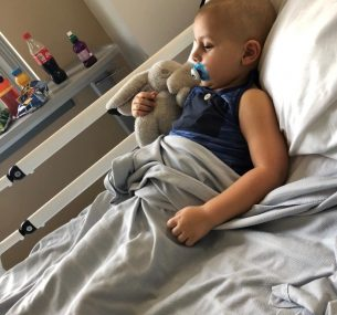 Boy in hospital bed with bunny toy