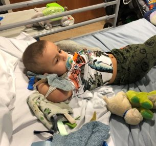 Boy in hospital bed with dummy and dinosaur t-shirt