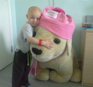 Ollie in hospital hugging a cuddly toy