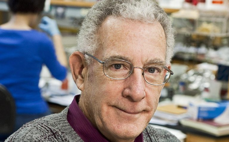 man with grey hair wearing glasses in a lab professot tom seyfried