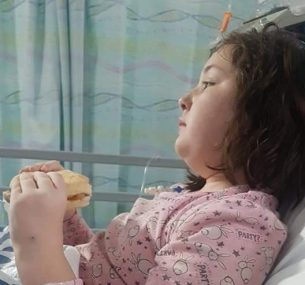Girl in hospital bed eating sandwich
