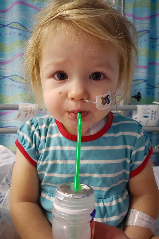 Izzy, while receiving treatment for leukaemia in hospital, is drinking through a straw.