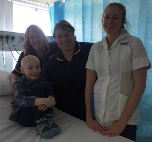 Boy in hospital bed surrounded by nurses