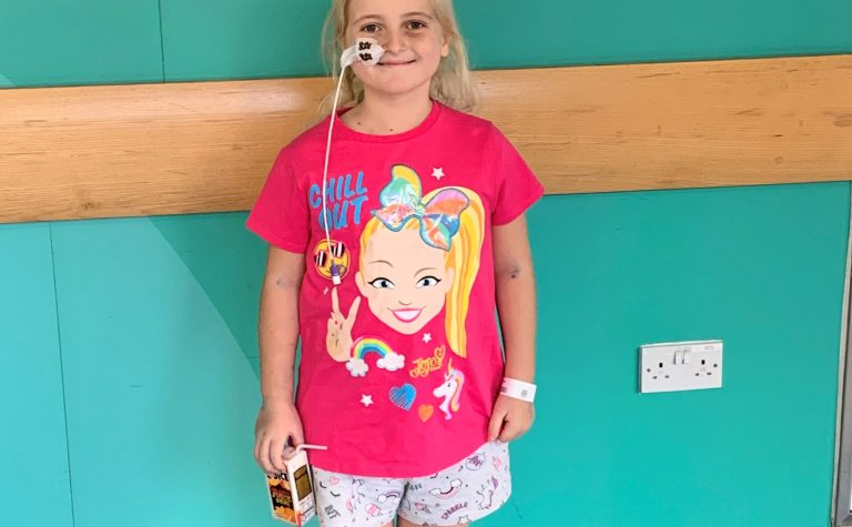 Girl in pin top in hospital with feeding tube