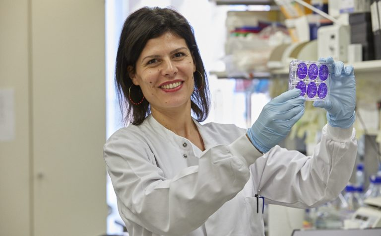 Female researcher smiling at camera holding a plate of cells