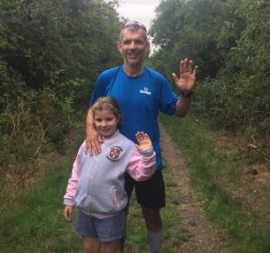 Adam at finish line smiling with daughter