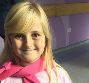 blonde girl with pink jumper wrapped around neck