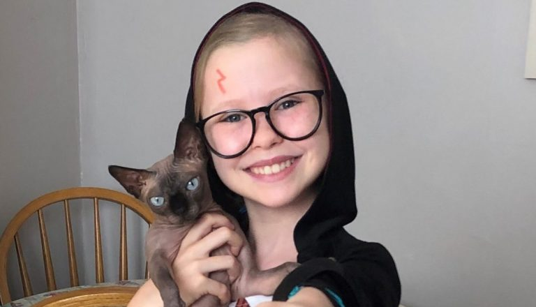 Girl wearing harry potter costume holding cat