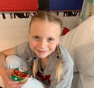 Blonde girl with plaits sitting in hospital bed with apple juice