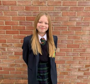 Girl in school uniform standing in front of brick wall