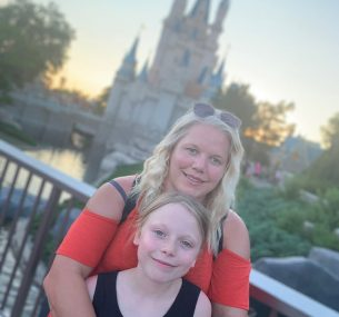 Mother and daughter standing in front of Disney castle