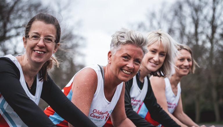 four marathon mums wearing vests smiling looking at camera