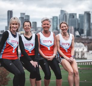 four marathon mums wearing vests smiling looking at camera sitting on metal handrail