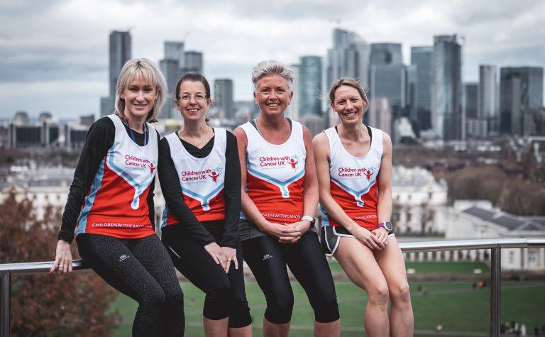 four marathon mums wearing vests smiling looking at camera sitting on metal handrail