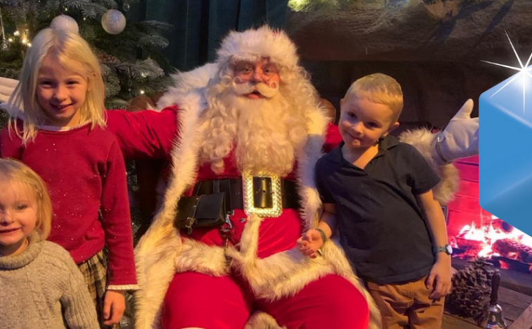 Christmas Grand Draw Father Christmas sitting with three children standing next to him