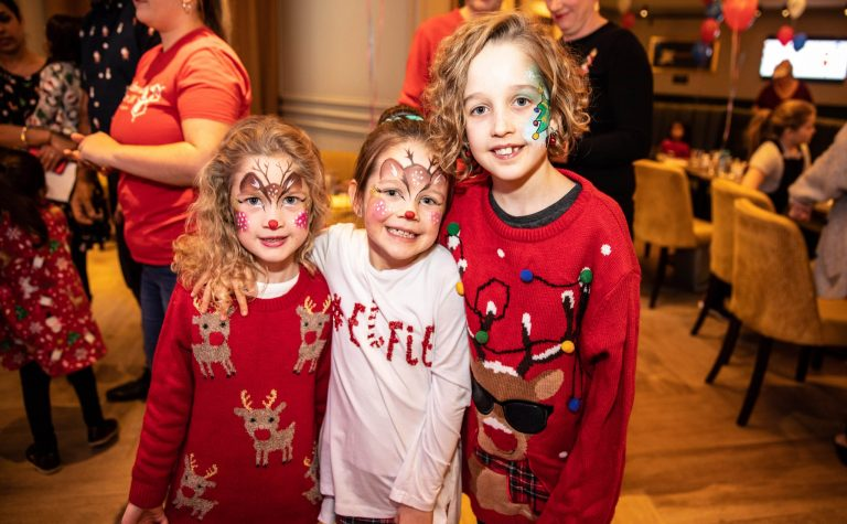 three girls with christmas jumpers at a party with their faces painted