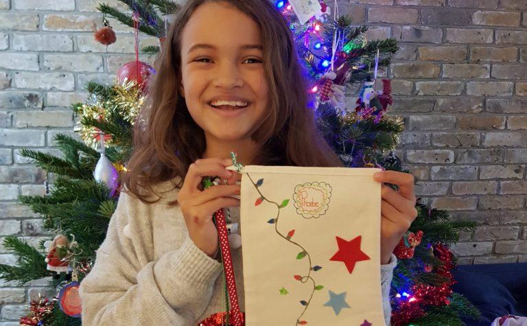 Phoebe girl smiling holding a christmas white stocking