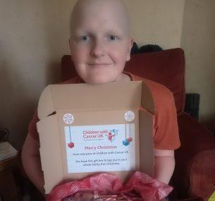 girl holding a christmas gift box smiling at camera