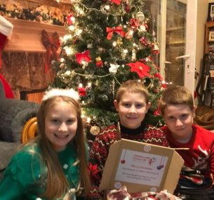 jacob and siblings by a christmas tree holding gift box