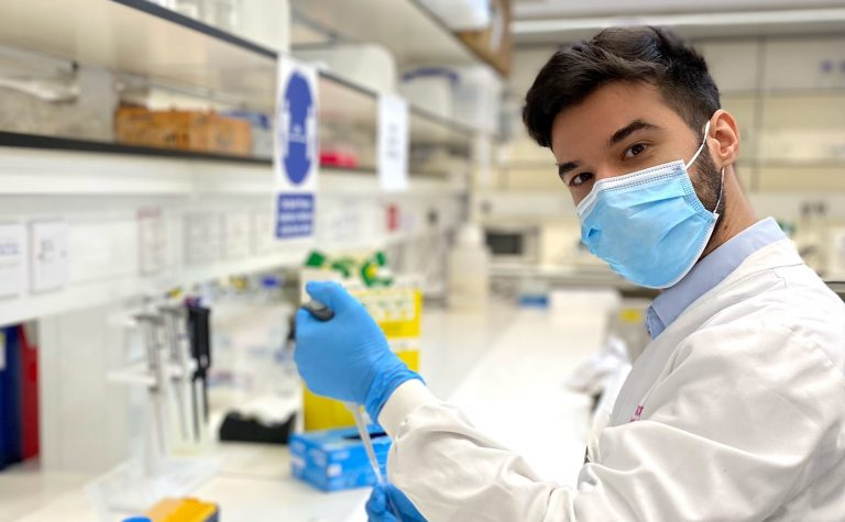 Researcher wearing mask and white lab coat holding pipette