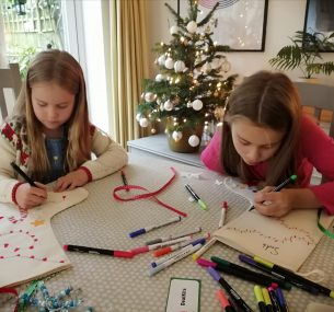 suki and sister sitting at table colouring in for christmas activities