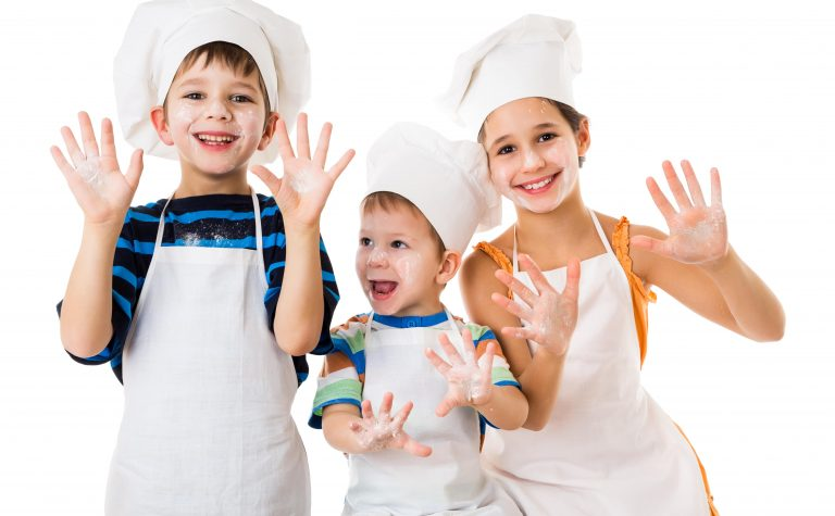 Children Baking wearing white chef hats and apron