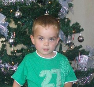 Harry with a green tshirt standing by a christmas tree holding teddy 1