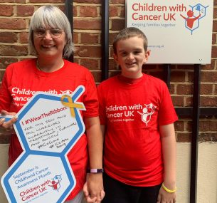 Teddy and mum in red tshirts holding Childhood cnacer awareness month frame