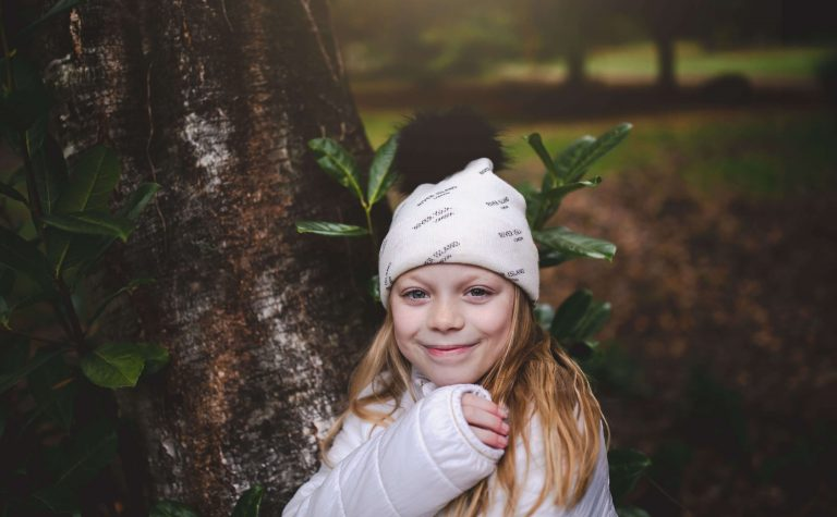 eve wearing a white hat next to a tree